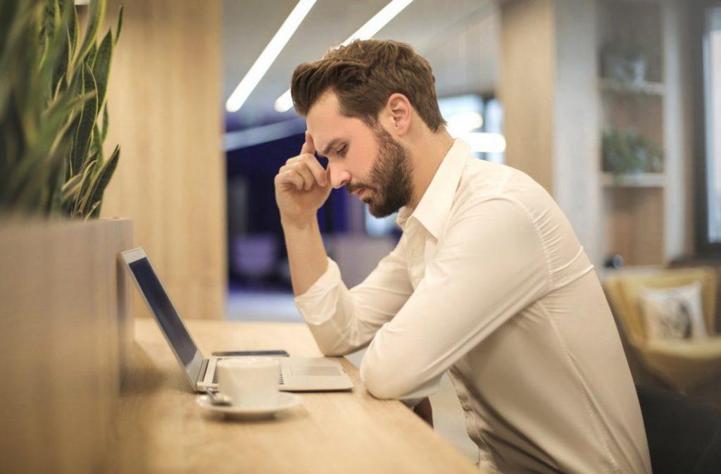 Ragazzo al lavoro con mal di testa